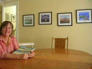 "Kristina Hagman at her dining room table, on the wall, four of her woodblock Prints: ""Thirty-Six Views of Mount Rainier"""